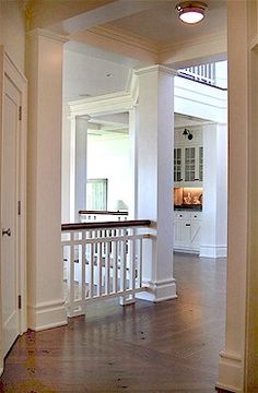 Perfect hardwood flooring, white columns, lovely mouldings.
