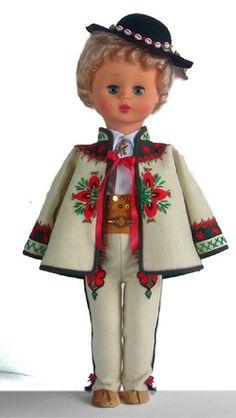 """Góral Podhalański  cucha i portki z sukna bogato haftowane, parzenica na spodniach, motyw kwiatowy - cucha, na nogach kierpce, na głowie kapelusz z piórkiem zdobiony """"muszelkami"""" Pracownia Lalek Regionalnych FOLKLOR"""