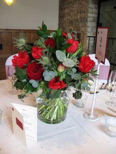 The tables in the Tythe Barn decorated with glass vases filled with posies of red winter flowers.