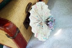 Love the rosette flowers made out of map pages. Easy party decoration! Via Kara's Party Ideas- www.KarasPartyIdeas.com. A site full of party ideas!