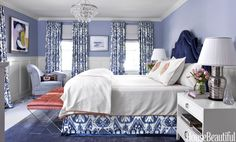 In the master bedroom, the palette is classic blue and white with a touch of salmon pink. The curtains and bed skirt are Brunschwig & Fils' Turkestan. Lamshop's Madison headboard in a Duralee velvet. Grace & Blake stools in Christopher Hyland's Rosello. Bedding, Leontine Linens.   - HouseBeautiful.com