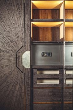 Showcase cabinet in stained eucalyptus featuring polished almond gold handle, embossed leather shelves and liquid metal safe.