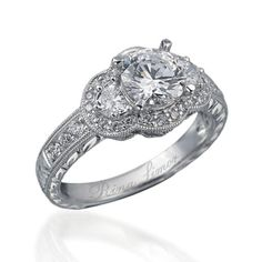 This Rina Limor engagement ring has an antique design and is set in platinum with three stones in the middle and smaller stones in the setting.