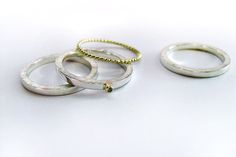 Silver and gold stackrings with a green diamond