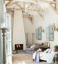 Lofty French farmhouse living room with grand chandelier, ceiling trusses, and dramatic fireplace. French Farmhouse Decor Inspiration Ideas will take you on a romantic tour of images capturing this charming decor style.