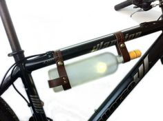 This handmade brown leather bicycle wine rack is perfect for taking wine with you on the go. It easily attaches to most bike frames with antique brass fasteners, while the hidden clamps hold the bottle securely. The olive oil-treated vegetable-tanned leather will only look better as it ages.    - Unisex  - Fits a 1-1.5 bike frame  - Adjustable to fit different types of 3″ bottles  - Hidden clamping system keeps clamp firmly in place  - Handmade in Montreal from oil-treated vegetable-tanned…