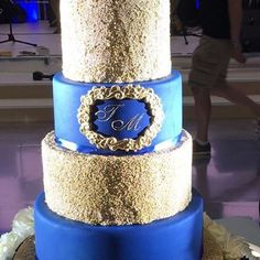 Gold sequins and initials. Another cake from the weekend, blue and gold theme, 5tier cake with a fresh flower base. #asianweddingcakes #sikhwedding #punjabiwedding #englishwedding #asianweddingcakes #uniqueweddingcakes #uniquecakes #cakedesign #uniquecakedesign #cakeart #tallcake #superiorcakes #luxuryweddingcakes #cake #weddingcake #weddingcakes #weddingdecor #Hangingcake #hangingweddingcake #suspendedcake #cremedelacakes #cakesofinstagram #hangingweddingcakes #suspendedweddingcake…