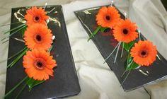 Orange gerbera buttonholes for mens wedding flowers, designed to match the bridal bouquet.