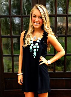 cute black dress with a teal statement necklace