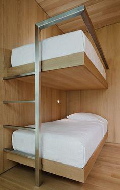 Дерево и двухъярусные кровати из нержавеющей стали с белым постельным бельем.