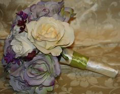 New  Rose 12 inch Round Bouquet, 3 cream specialty real touch roses with 8 lavendar specialty real touch roses, 3 white roses, purple accent flowers, hand tied with white satin ribbon, accented with green ribbon. Contact us for Custom Bridal Bouquets.