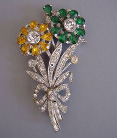 MASTERCRAFT flower brooch of green, clear and yellow rhinestones set in pot metal - 1940