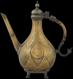 Michael Backman Ltd - Engraved Mughal Ewer North India 18th century  height: 33cm, width: 32cm, weight: 3,149g  This northern Indian ewer is of typical form. The tear-shaped body stands solidly on four small feet, and the neck tapers and then widens to a lidded mouth.  But several details mark this ewer out as a better quality example. It is larger than most similar examples, and of a good weight. The spout is strong and lightly  faceted. The design work on the body is of better quality than…