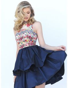 Multi-colored floral embroidery adorns the bodice with round collar neckline, cut-in shoulders and cutout back of this Sherri Hill 50638 short dress. The gathered, dual tiered navy skirt with an above the knee hemline completes the A-line silhouette.