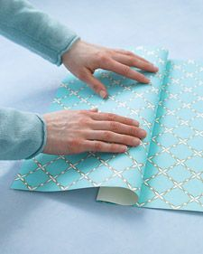 I'll never wrap a gift the same way again. [Wrap a gift with a pocket for holding the card.] COOL!