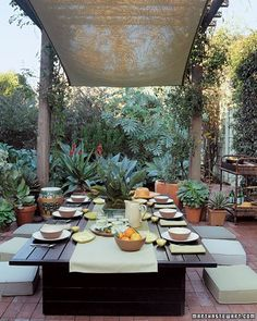 This low table is surrounded by Japanese-style cushions. Remove the table's top and it converts to a daybed, the cushions becoming a mattress. A scrim of Westringia fruticosa, Melianthus major, and Eugenia creates the room's walls; succulents soften the bricked terrace.