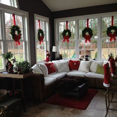 Love the wreaths suspended with red ribbon in the windows of this sunroom decorated for the Christmas season.
