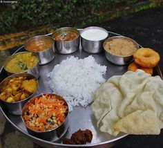 "A South Indian Thali is made up of a selection of various South Indian dishes. There really is no ""rule"" as to what constitutes a Thali (read: Thaalee). You're just going to have to fill it up with..."
