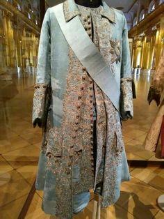 На коронацию Екатерины I в 1724 году для Петра I был сшит небесно-голубой костюм и надетый после смерти императора на Восковую персону.  Согласно легенде, костюм императора вышивала собственноручно Екатерина Алексеевна. Вне всякого сомнения, вышивка была выполнена мастерами высочайшего уровня, но, возможно, будущая императрица вышила маленькую корону, украшенную ромашками, скрытую от глаз. Эта корона, находящаяся на шерстяной ткани между подкладкой и верхней тканью, была обнаружена во время…