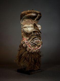 """Afrikaanse Tribal GUERE masker. Liberia.  Hoogte 33 cm.  baard van 20 cm.Breedte 185 cm.Diepte 12 cm.Hout ijzer textiel kralen koperen nagels noten vezel en verfOp een zwart geschilderde eiken houten staan.Wonen langs de westelijke rand van Ivoorkust delen de Guere en hun buren de Wobe talrijke gewoonten en overtuigingen. Hoewel ze aparte stammen zijn worden de twee volkeren vaak aangeduid als de We wiens naam betekent """"mannen die gemakkelijk vergeven.""""Volgens Jean-Baptiste Bacquart in zijn…"""