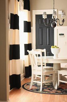 Oatmeal walls, black door, stripe curtains
