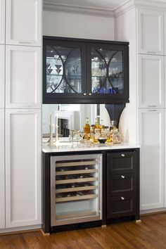 This stylish black wet bar makes a statement in a transitional white kitchen. The bar area features a sleek wine fridge, a hidden ice machine and glass-front cabinets to house drinkware. Layout Design, Design Ideas, Design Design, Interior Design, Small Bars For Home, Glass Front Cabinets, Black Cabinets, Kitchen Cabinets, Modern Cabinets