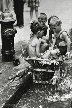 Kids from the Lower East Side - New York City 1937. This charming image captures the antics of children in the lower east side of New York City in the United States in 1937. Sat in a wheel barrow, the four youngsters share a giggle as they make the most of splashing around in water on a hot American day. Its timeless black and white photography capture the essence of fun, youth and innocence.