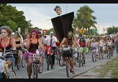 In this Sunday, Oct. 20, 2013 photo provided by the Florida Keys News Bureau, participants in the Zombie Bike Ride pedal down the Florida Keys Overseas Highway in Key West, Fla. Thousands of costumed bicycle riders participated in the offbeat event. Key West's annual Fantasy Fest costuming and masking festival, that began Friday, Oct. 18, continues through Sunday, Oct. 27.