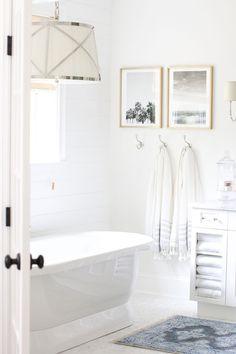 White bathroom, large light fixture over tub, bathroom wall decor, bathroom pictures, bathroom hooks, blue rug in bathroom, free standing tub