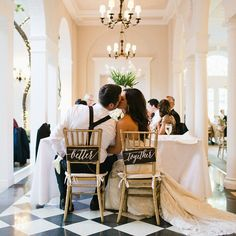 This wedding photo is too cute; especially loving the 'better together' signs hung from the back of the gold chairs.