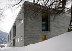 The building is partially submerged into the hillside and is covered by a grass roof, making it almost invisible from behind.