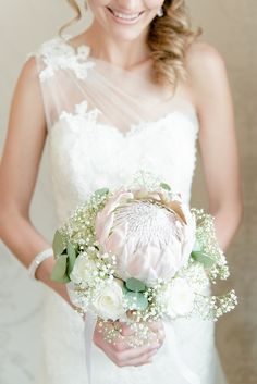 Breathtaking Wedding Bouquet Recipe: Simple but striking - a large blush pink King Protea surrounded by delicate babys breath, eucalyptus and white roses. Lace Bouquet, Protea Bouquet, Blush Bouquet, Bridesmaid Bouquet, Bouquet Flowers, Protea Wedding, Sage Wedding, Wedding Bouquets, Wedding Flowers