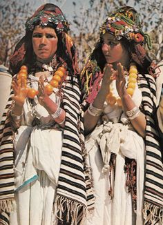 Berber girls clap to the rhythm of village musicians at a festival in the Atlas Mountains. The distinctively striped wool shawls they wear identify their clan affiliation. (credit: George Holton)