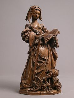 A German walnut figure, c.1530, representing Saint Catherine of Alexandria; she is shown with her symbolic attributes, a broken wheel, a sword and a holy book; a pagan philosopher lies beneath her feet as a symbol of her triumph. (Metropolitan Museum of Art)