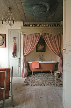 """The cast iron tub was painted with an old rose lacquer and placed under a canopy. A patchwork """"rug"""" of old cement tiles."""