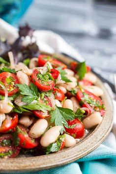 A close up shot of tomato & white bean salad on a brown plate.