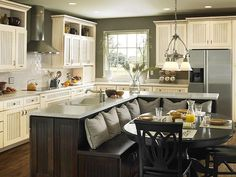 I love the layout of this kitchen, with the banquet style seating on the other side of the island. Very cozy!
