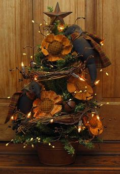 Primitive sunflower crow christmas tree in rusty bucket with white lights, grapevine, and pip berries