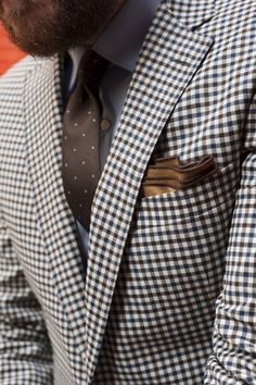 A lovely mixture of soft colours and soft textures. end-on-end dove grey shirting, a subtly spotted chocolate silk tie, a handkerchief showing its rolled edge for fullness, and a neutral gingham checked jacket.