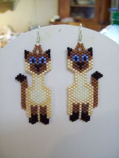 Siamese Cat Earrings are custom made with Biege, off white, brown, black and blue Delica beads. Very cute earrings.They are about 2 in. long with silver wires on them can be changed to post or clips. If you have any Questions just ask. Pony Bead Patterns, Beaded Jewelry Patterns, Beading Patterns, Seed Bead Jewelry, Bead Jewellery, Seed Bead Earrings, Hoop Earrings, Beaded Earrings Native, Beaded Crafts