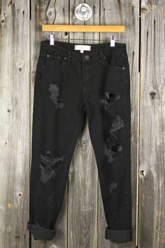 "Our black rinse boyfriend jeans feature destructed tears and a zip-up fly. · Loose Fit Design + High Waist · 29"" Inseam, 9"" Rise · Both Legs Feature Horizontal Rips + Holes"