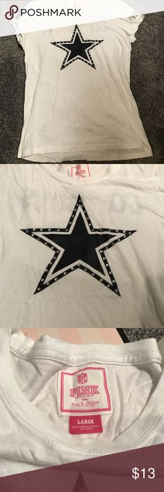 PINK by Victoria's Secret Vintage Cowboys T-Shirt PINK by Victoria's Secret Vintage Dallas Cowboys T-Shirt. Size L. Used but good condition. No stains or holes. Some of the lettering does have cracks in it, but this isn't too bad. Cowboys Star logo in the middle of tee in the front. Has crystals embroidered around it and are all still in tact. Left arm has PINK written in silver/gray. Right arm has 60 in navy and silver. Back has Cowboys in silver and bottom right has navy football that says…