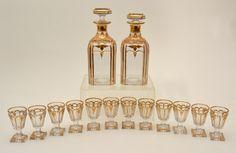 BACCARAT – Belíssimo conjunto de dois licoreiros guarnecidos de doze cálices, em fino cristal francês e ornamentados por filetes e guirlandas em ouro. França. Séc. XIX. 21 cm e 7,5 cm. Base R$2.000,00. Nov16