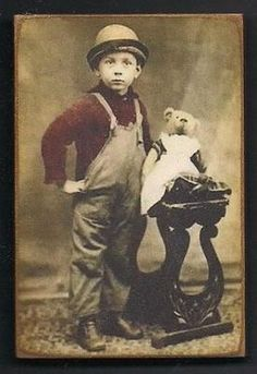 Tinted photo, boy in overalls with Teddy bear wearing a dress, circa 1900.
