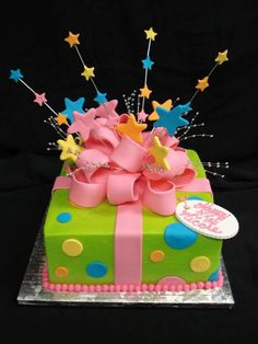 This birthday present is bursting with stars in this green, blue, yellow, and orange polka-dotted cake, complete with a large pink edible bow. @PartyFlavors #PartyFlavors