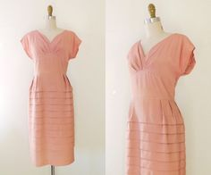 A lovely 40s dress in a beautiful blush pink. The dress has soft draped sleeves, a gathered bust, a flattering slim waist, and a tier of horizontal pleats throughout the entire skirt.  --L A B E L--  None  --M E A S U R E M E N T S--  bust: 18 with extra room due to the folds in the bust waist: 15 hip: 21/free length: 41 from shoulder to hem best fit: L   -- D E T A I L S--  closure: metal zip midway up the back material: rayon crepe  --C O N D I T I O N--  Great vintage condition. There...
