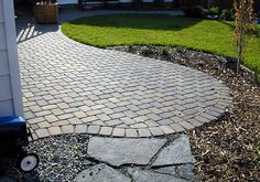Some stepping stones to a paved area for a table might help with the transition from the old driveway pavers to a new style of paver.