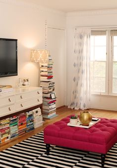 Stacks and stacks of books look very much at home with this raspberry pink tufted ottoman and striped area rug.