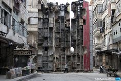 SYRIA, ALEPPO : A young boy walks past a makeshift barricade made of wreckages of buses to obstruct the view of regime snipers and to keep people safe, on March 14, 2015...