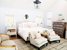 Bedroom with white walls, white bedding, beige bed frame, beige striped chairs, patterned dresser, light wooden coffee table, light pink patterned pillows, beige and black rug, white lamps and bedside tables, and a glass and black light fixture